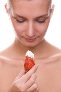 beautiful young naked girl with red juicy strawberry in her hand